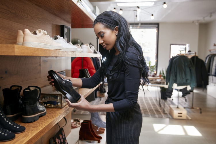 Young black woman looking at shoes on display in a shop